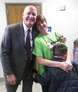 Superintendent Tom Enslen gives Lee PE teacher JoAnne Desy a hug after her last Jump Rope for Heart event.