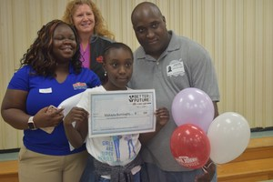 Makayla Burroughs, a fifth grade student at Harry E. James Elementary, stands with her father and representatives from the Better Future Fund, after being named a  winner on April 17.