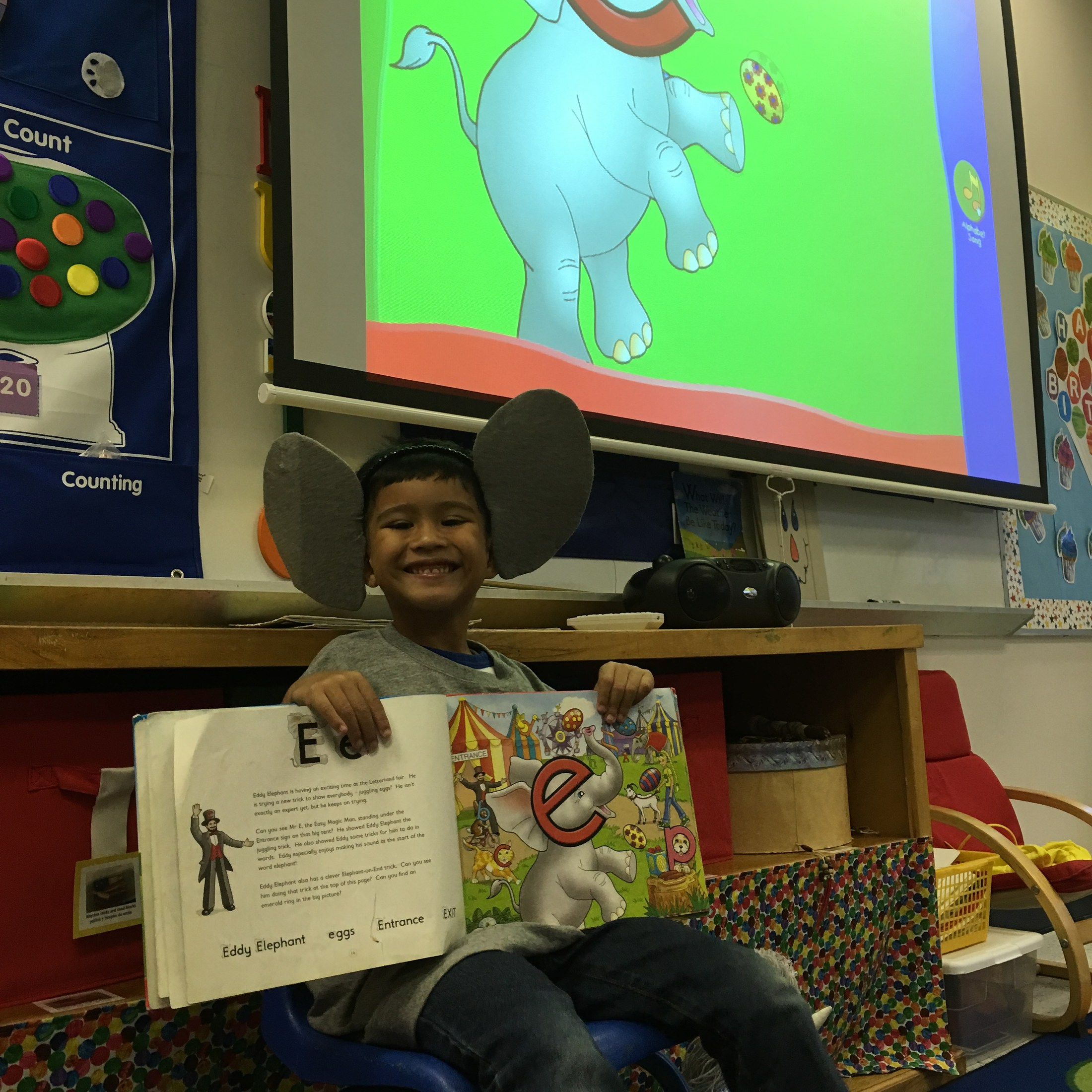 student reading book to class