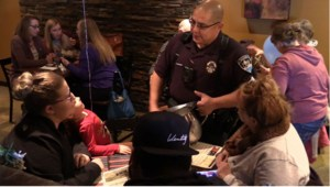 Photo of a Moses Lake Cop at Rock Top, tending to a family at their table.