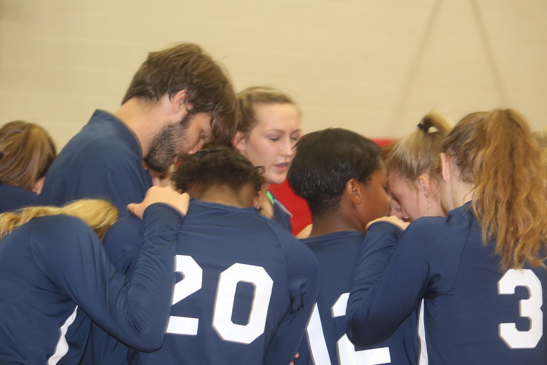 team praying together in huddle