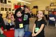 girl raising hand while her friends smile in kindergarten sitting on floor