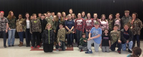 Students grouped in the cafeteria wearing cammo showing their support for a student struck with cancer.