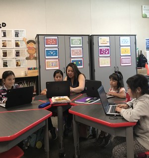 De Anza Elementary third-grade teacher Patricia Shelton works with children in her tech-infused classroom, which contains modular furniture that can be quickly configured for different sized collaboration groups.