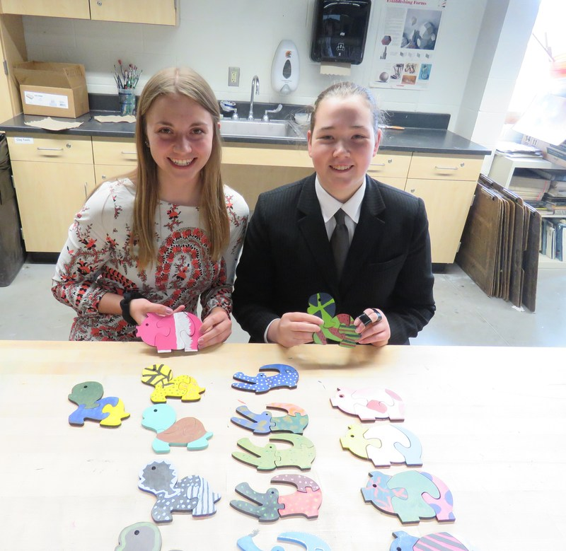 Monica Bluhm (left) and Samantha Craven get ready to pack up the wooden puzzles they've made and will donate to DeVos Children's Hospital.