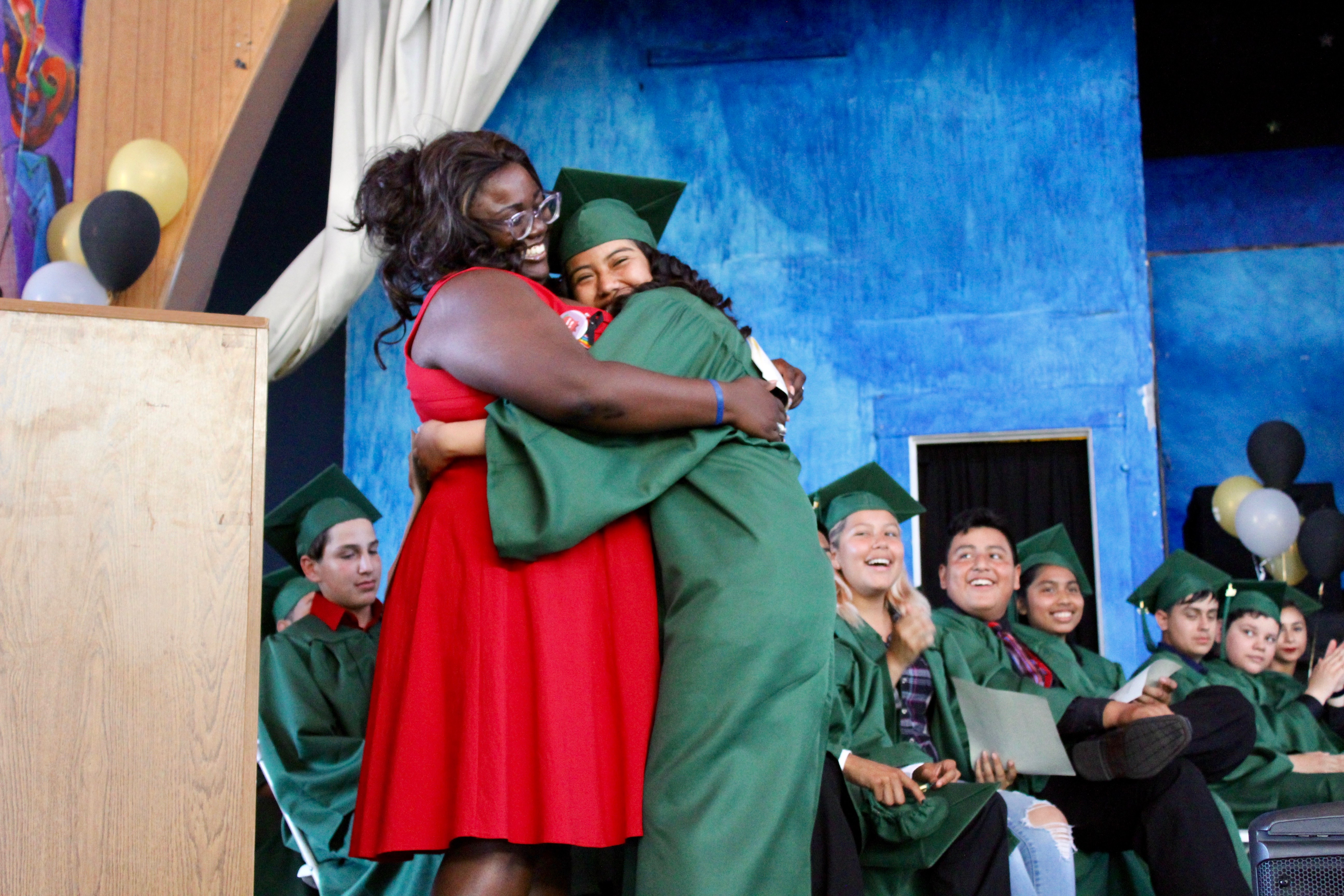 Teacher hugs student during graduation ceremony