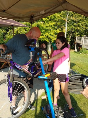 A girl works with a man to repair a bike