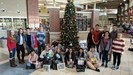NHS Students pose with all of the toys they bought by the Christmas tree in the school.