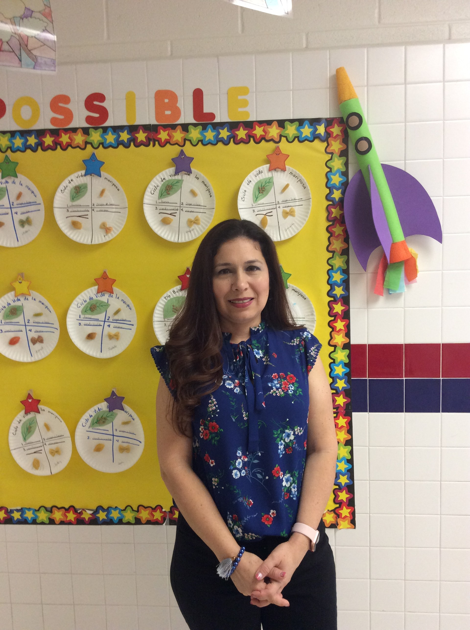 Mrs. De La Rosa posing for a picture in the hallway.