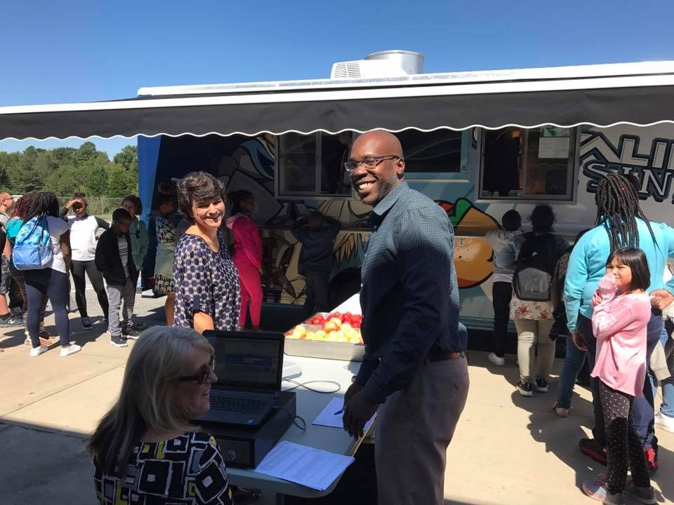 Food service employees greeting students with a smile.