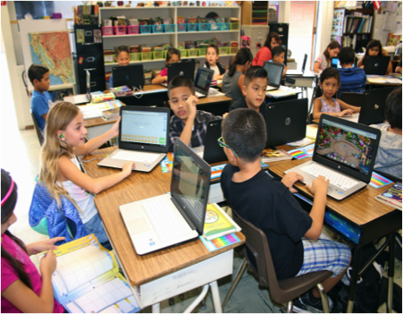 Students studying on Chromebooks in the classroom.