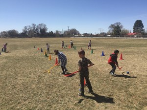 Students playing field hockey.