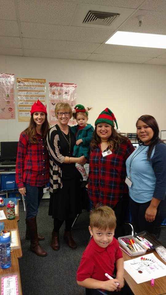 Mrs. Walker with a para and two parents dressed as elves.