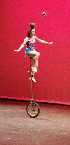 chines acrobat performing balancing plates while on a bike