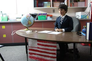 A student sits at a desk with the American flag as part of night at the museum.
