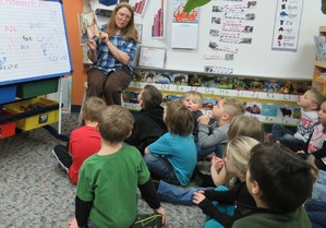 A preschool teacher reads a book to her students.