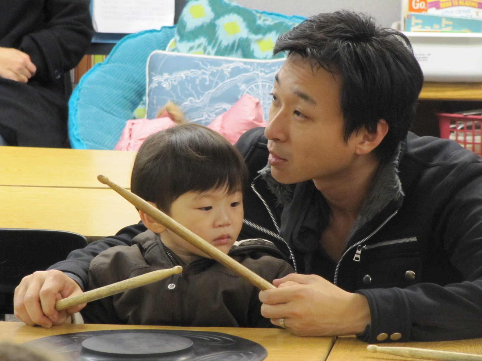 A young boy and his fother using drum sticks.