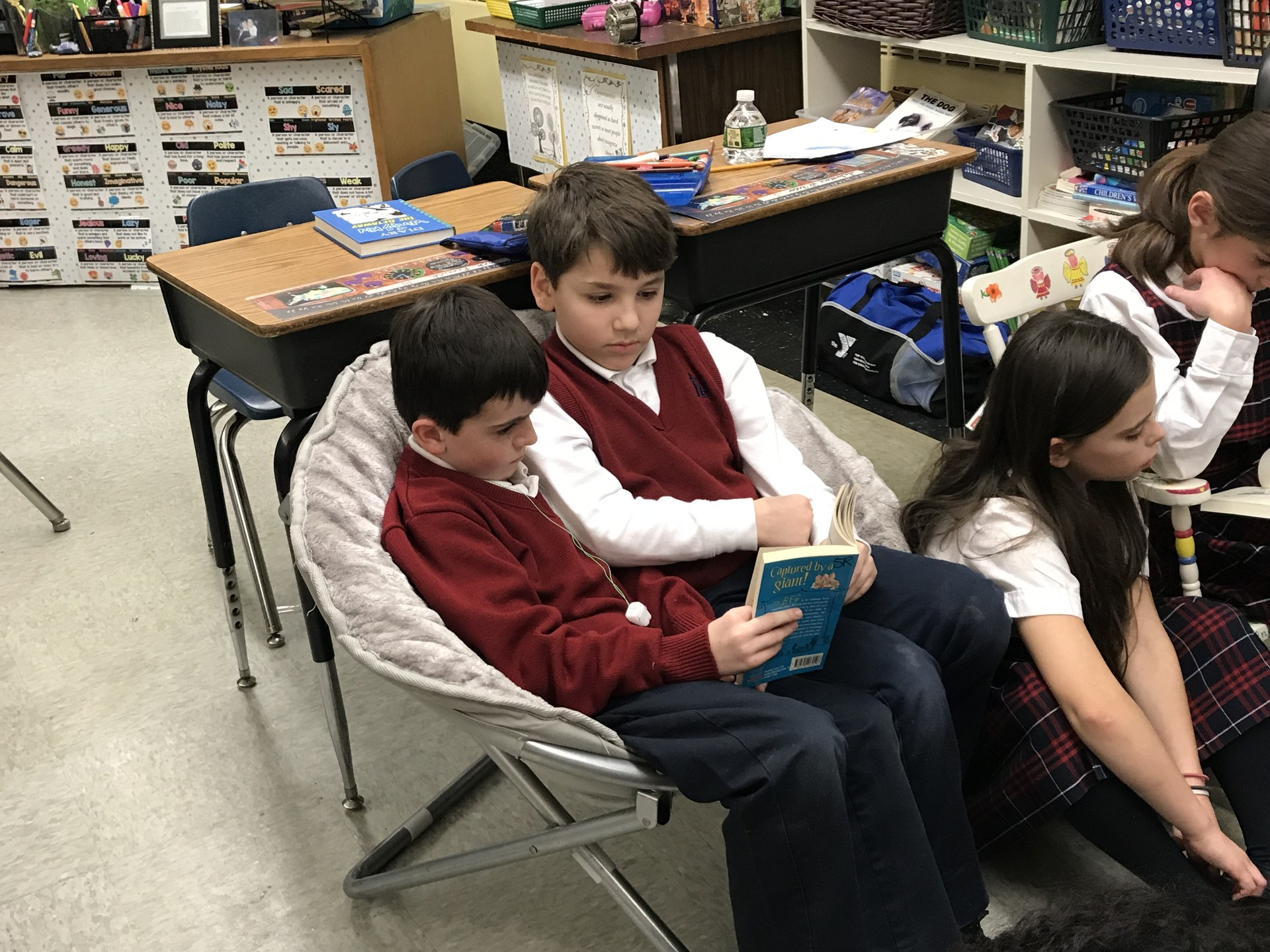 Two students sit next to each other and read