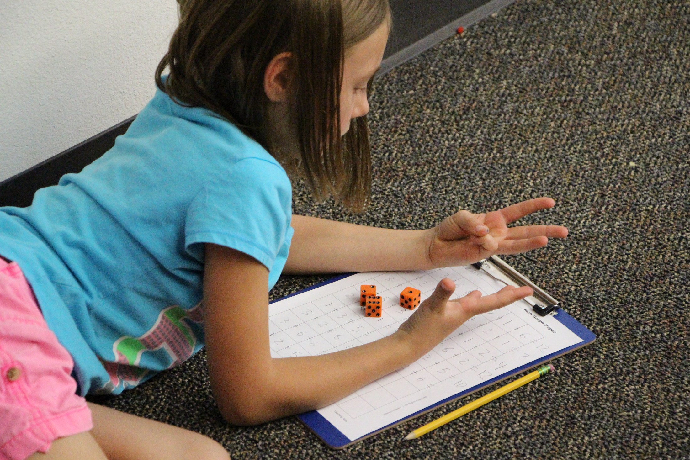 A student counts on her fingers as she works on a math worksheet.