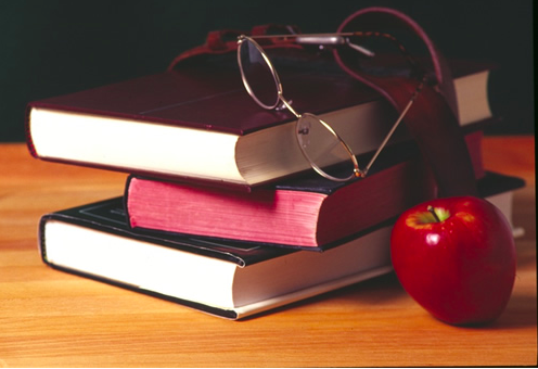 stacked books with glasses and an apple