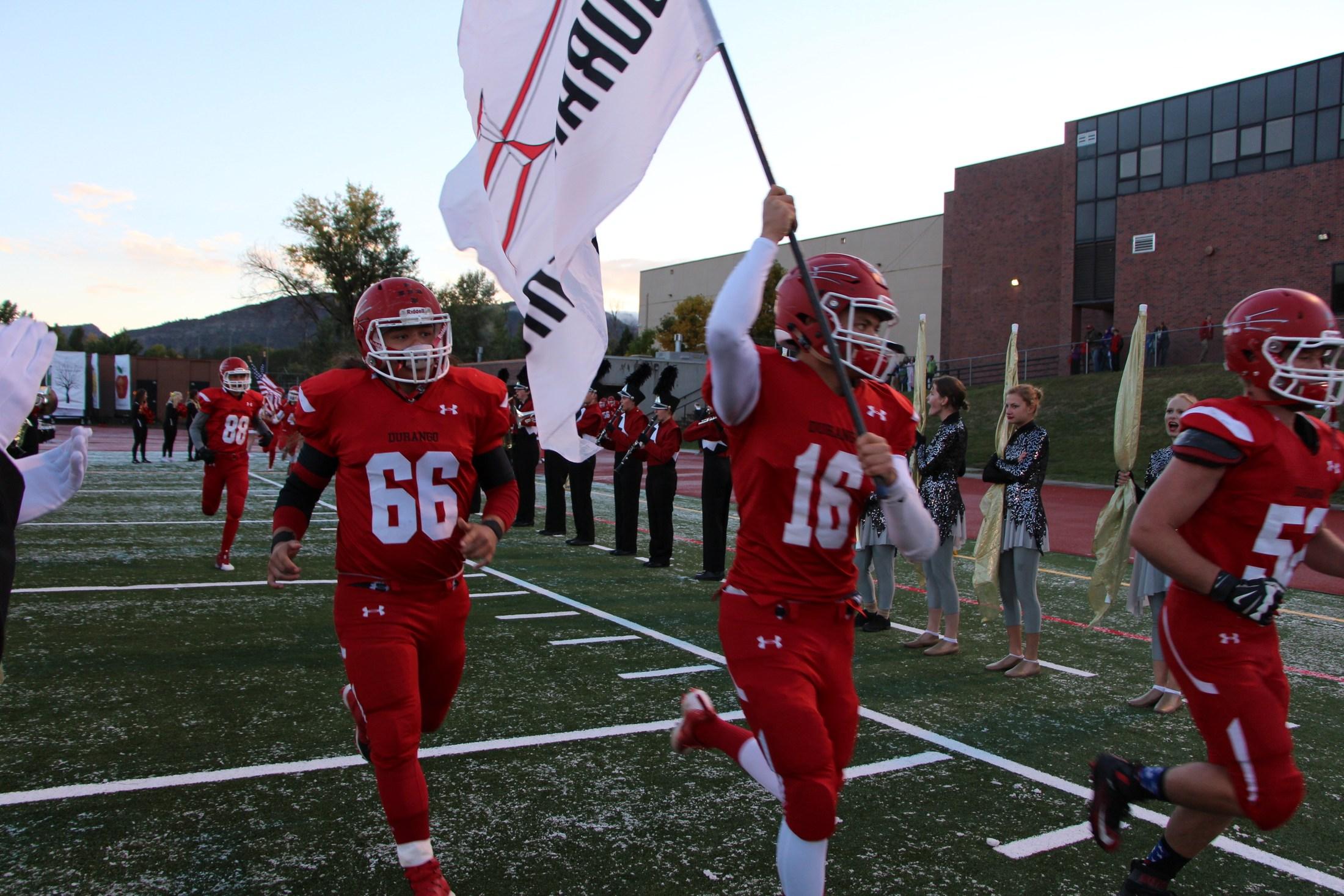 Demon players waving Demon football flag across football field