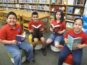 Bryan students in library holding books.