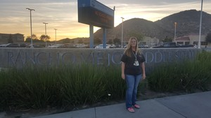 Juanita Weis posing in front of the Rancho Viejo sign