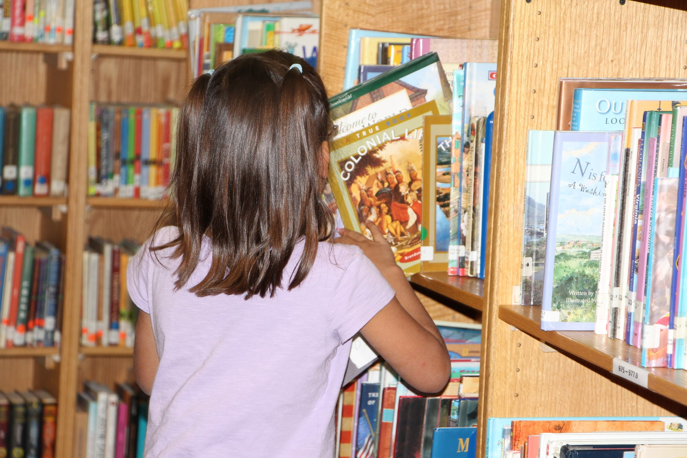 Child selecting book.