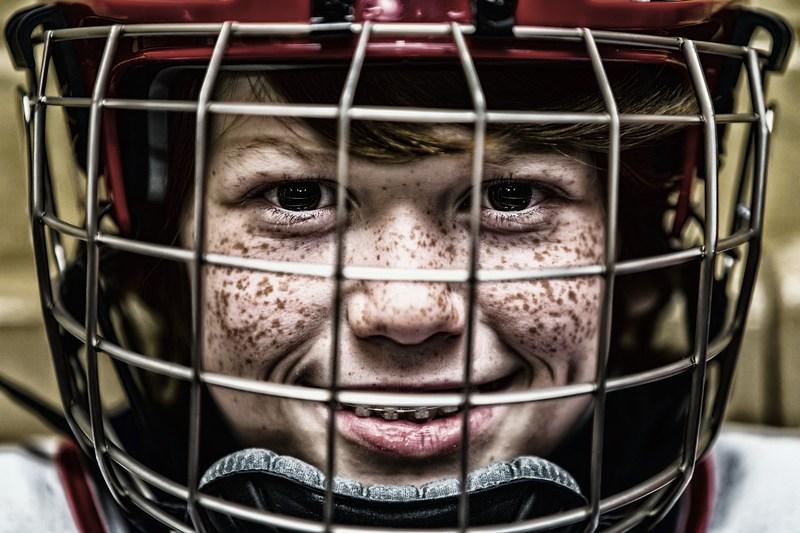 Kid wearing hockey helmet.