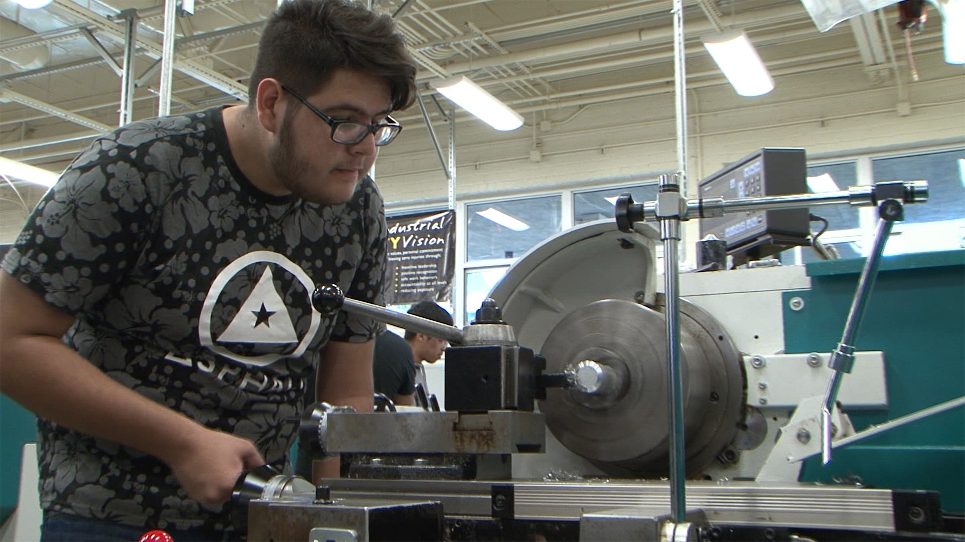 student using a machining tool in manufacturing class