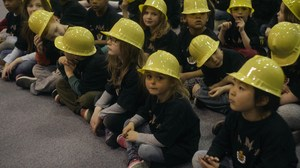 Students sitting in the gymn wearing hardhats and listening.