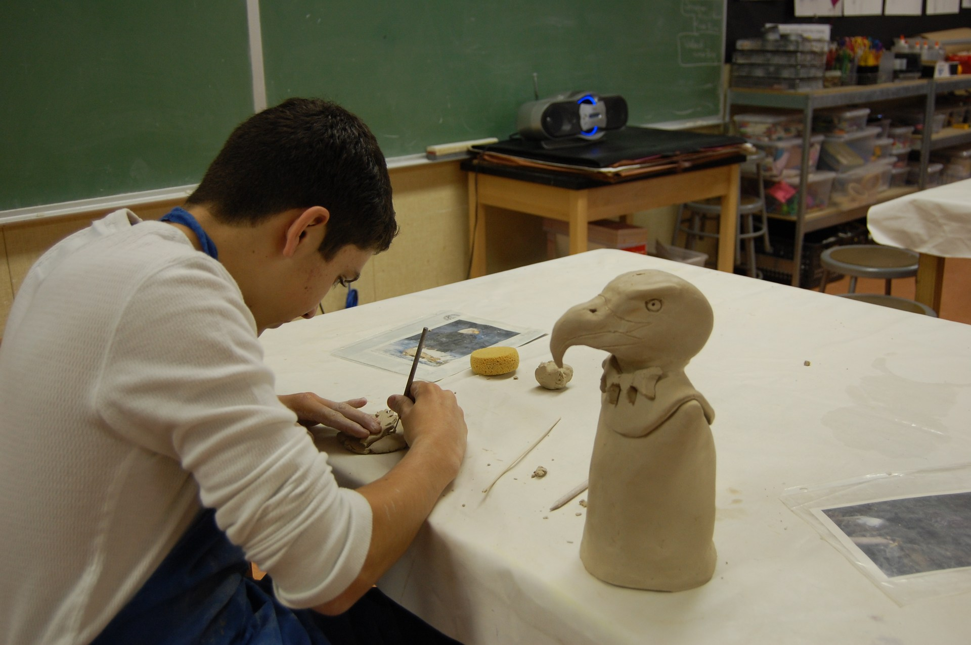 Art student carving clay sculpture