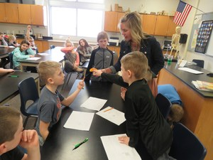 Page students work through science problems together.