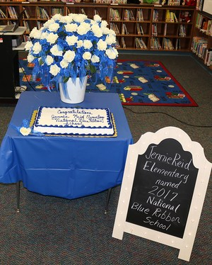 Rose bouquet, cake and sign announcing Jennie Reid Elementary School as a National Blue Ribbon School