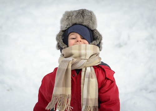Kid bundled up in winter hat and scarf.