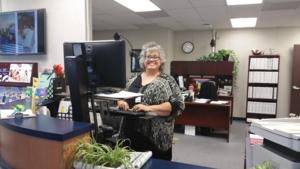 Yolanda Camacho standing at her computer.