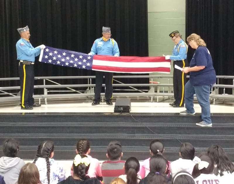 Showing the students how to fold the flag properly, and its meaning.