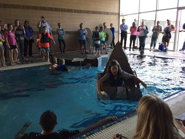 Students sinking in pool in a cardboard boat