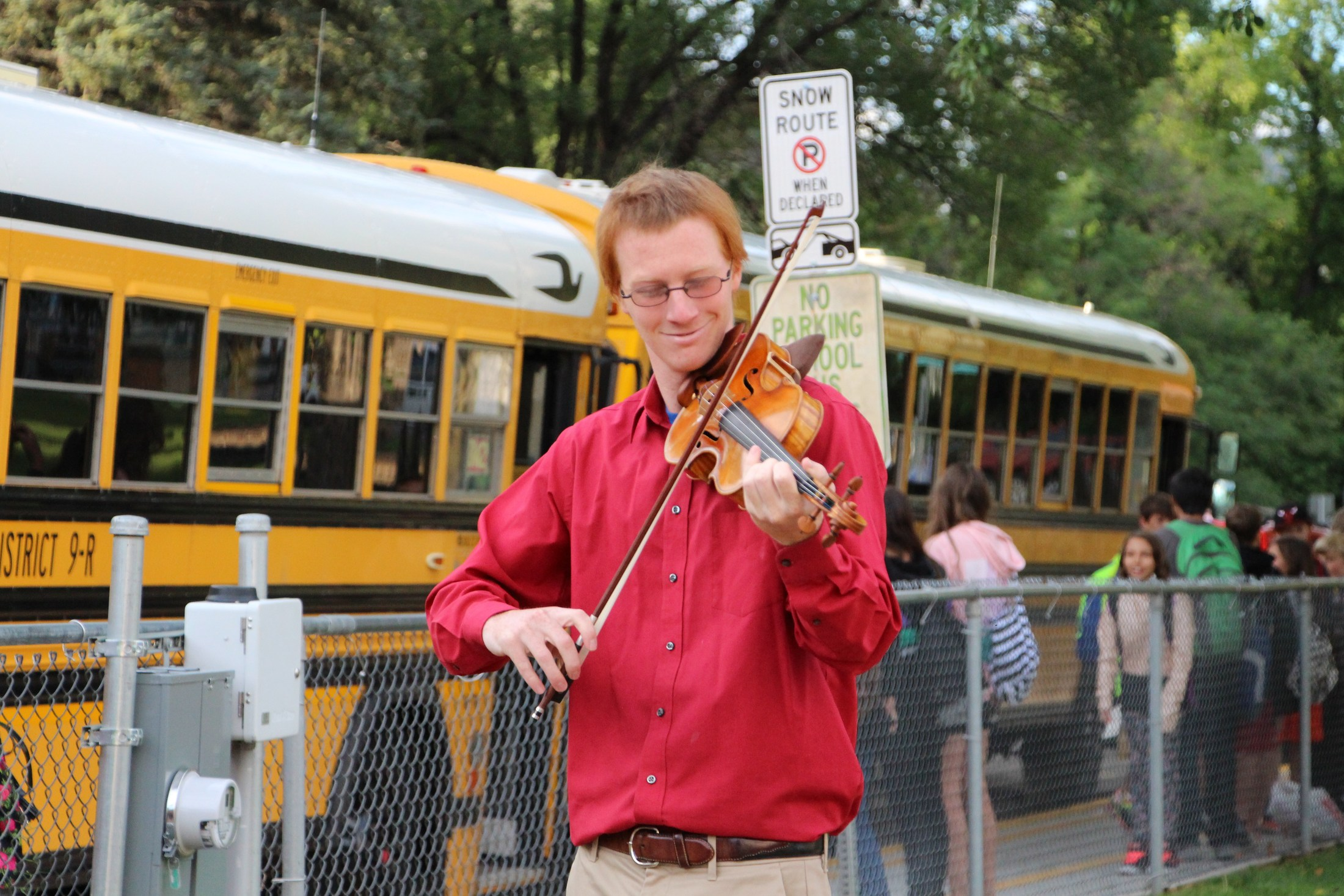 Rusty Charpentier plays violin for students arriving at the first day of school.