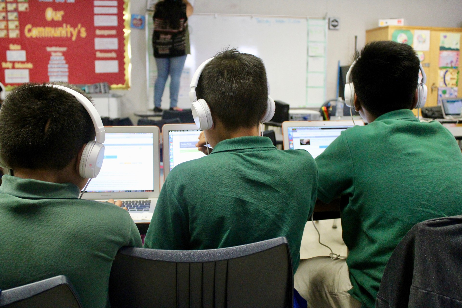 students wear headphones as they work on computers