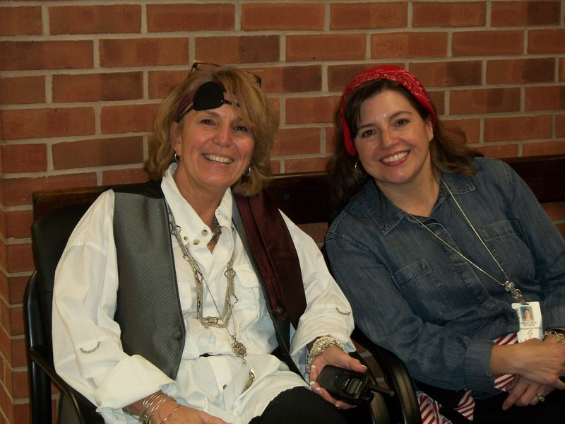Two staff members dressed as pirates are sitting in the hall outside the school office.