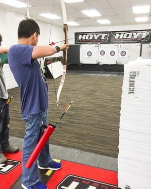 Students with bow shooting an arrow at a distant target.