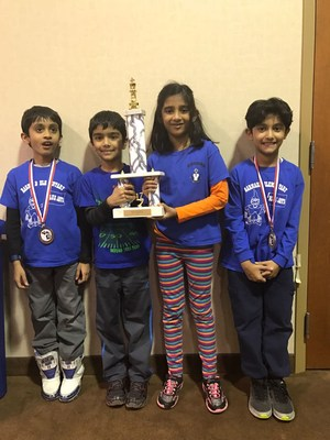 4 students holding a chess trophy
