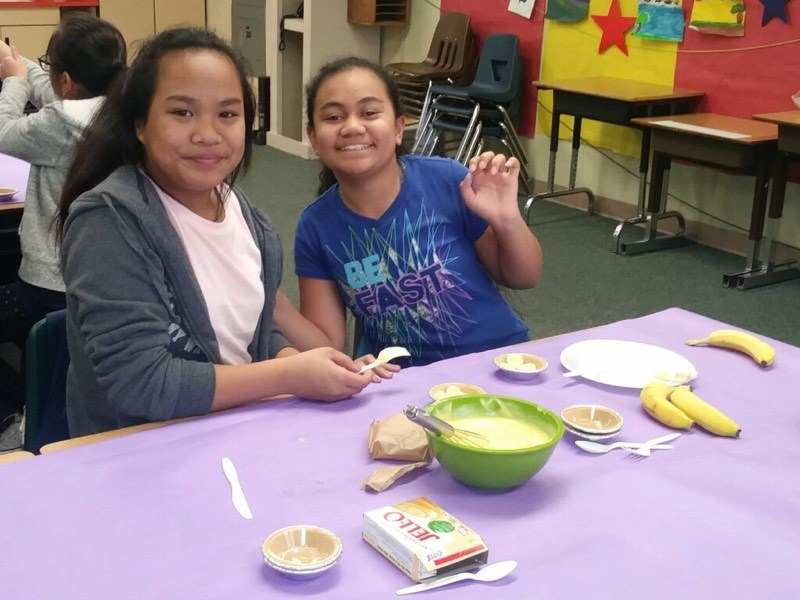 two students sitting at a table making a mini pie