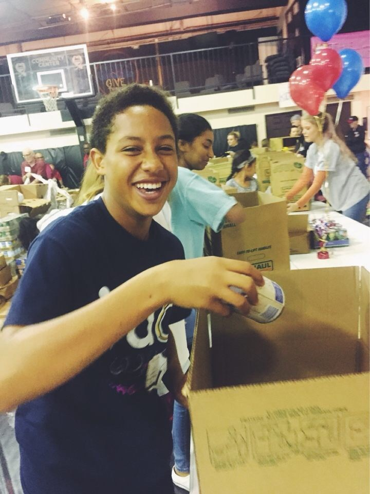 Smile club student packing boxes of supplies
