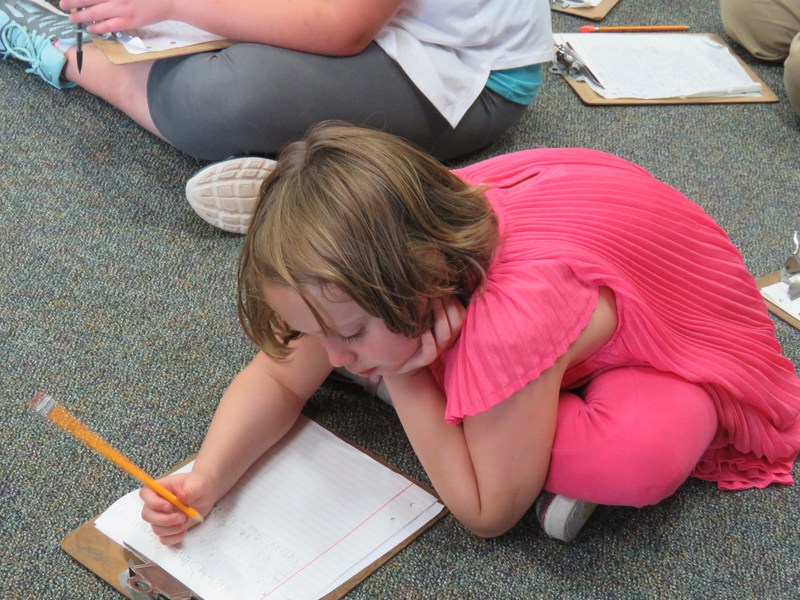 A Page Elementary student revises her writing after learning tips from an author.