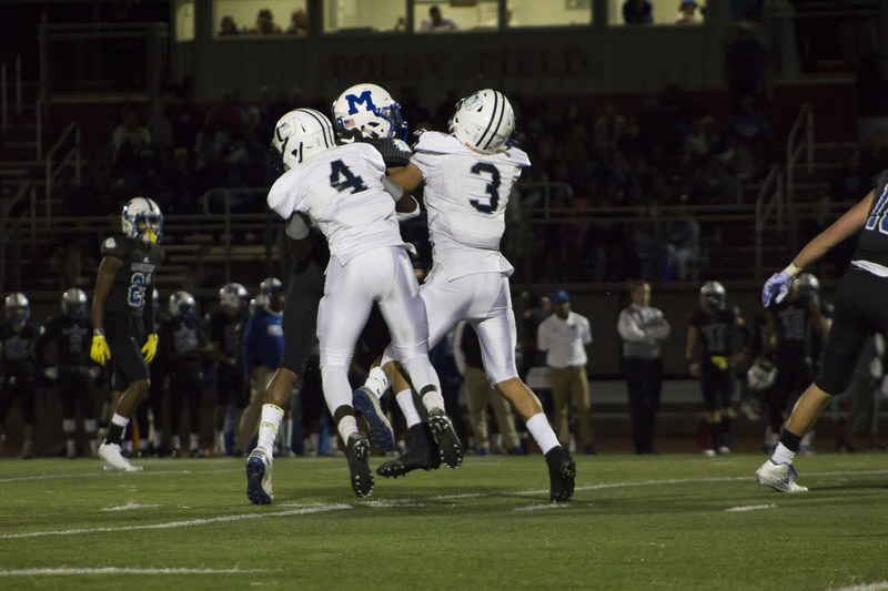 two uchs football players trying to stop a montclair football player