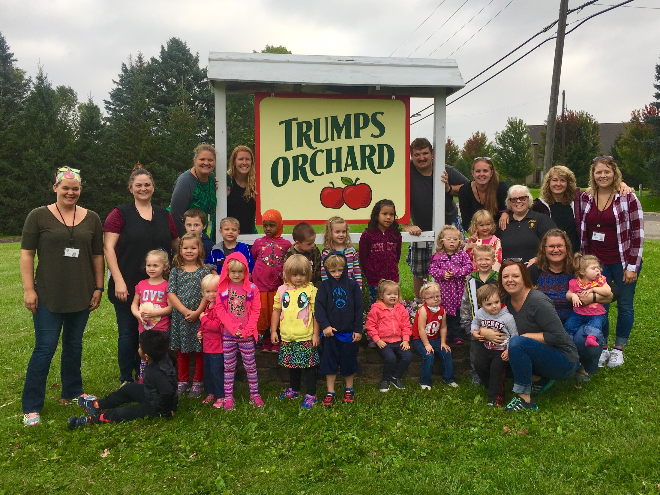 a large group of students and staff standing in front of an apple orchard sign.
