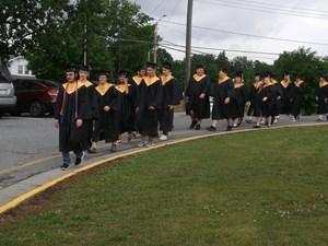 Graduates march through parking lot.