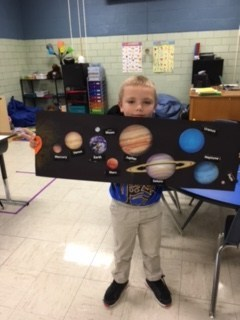 Student holding picture of planets